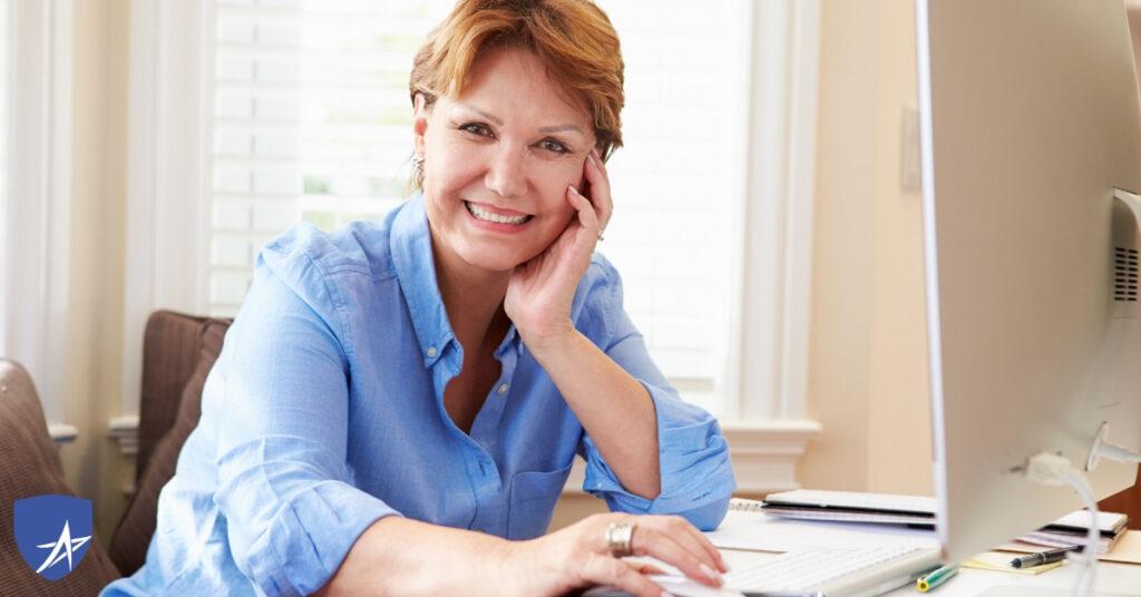 senior woman at computer smiling into camera
