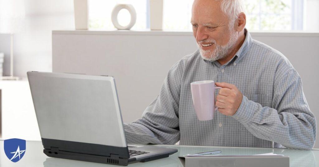 senior man drinking coffee at his computer