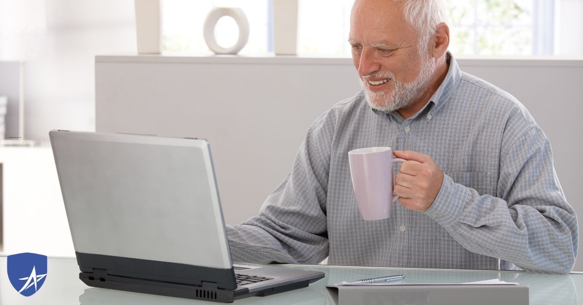 senior man drinking coffee at his computer