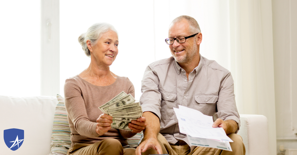 senior couple holding money smiling