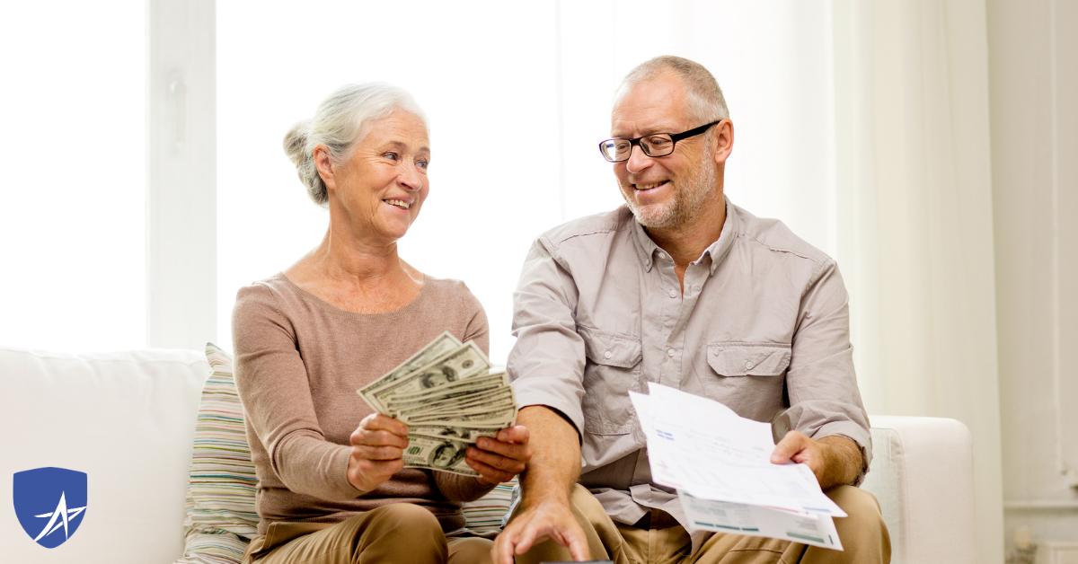 senior couple holding money smiling