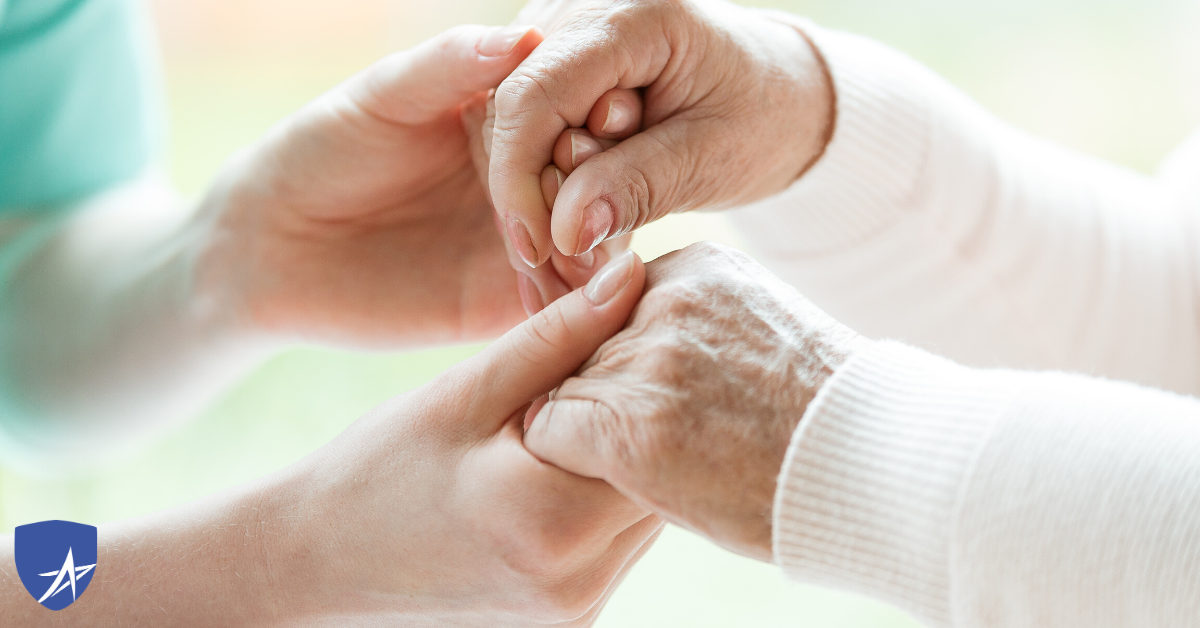 holding the hands of senior in hospice care